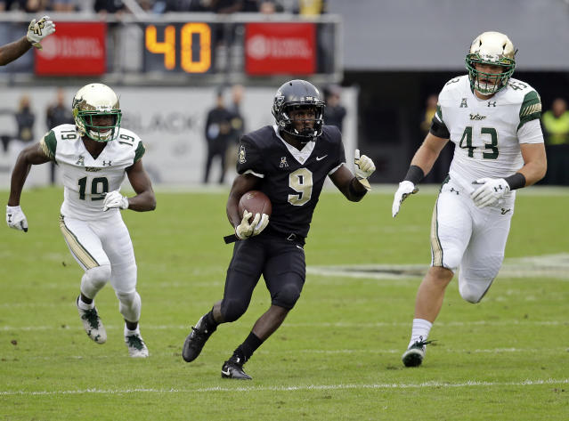"Central Florida running back <a class=""link rapid-noclick-resp"" href=""/ncaaf/players/270179/"" data-ylk=""slk:Adrian Killins Jr."">Adrian Killins Jr.</a> (9) runs for yardage between South Florida cornerback Ronnie Hoggins (19) and linebacker Auggie Sanchez (43) during the first half of an NCAA college football game, Friday, Nov. 24, 2017, in Orlando, Fla. (AP Photo/John Raoux)"