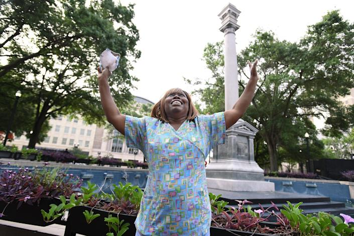 Jacksonville resident Denise Hunt celebrates the partial removal of a Confederate monument from Hemming Park on Tuesday.