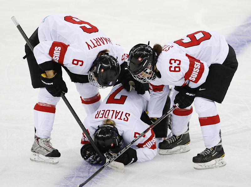 Julia Marty (6) and Anja Stiefel of Switzerland (63) check on their injured teammate Lara Stalder during the third period of the game against USA at the 2014 Winter Olympics women's ice hockey match at Shayba Arena, Monday, Feb. 10, 2014, in Sochi, Russia. (AP Photo/Petr David Josek)