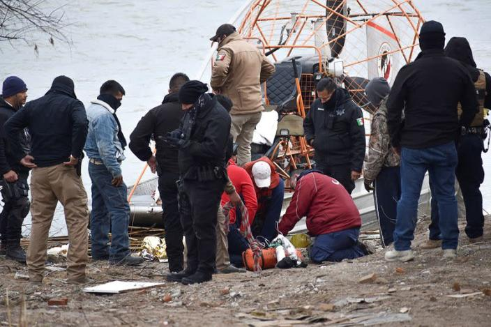 FILE PHOTO: Paramedics check the body of a Honduran migrant child, who drowned while crossing the frigid waters of the Rio Grande river from Mexico into the U.S. with his mother and sister, according to local media, in Piedras Negras