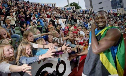 Young spectators cheer and try to touch Jamaican sprinter Usain Bolt after he won the men's 100m at the Diamond League