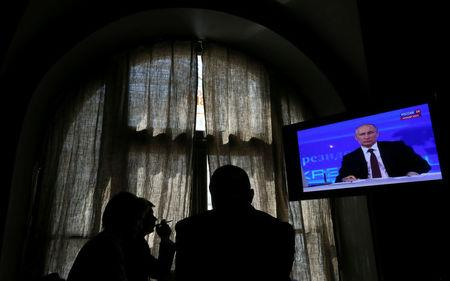 FILE PHOTO: People look at a screen at a media centre during Russian President Vladimir Putin's live broadcast nationwide phone-in in Moscow, Russia April 17, 2014. REUTERS/Sergei Karpukhin/File Photo