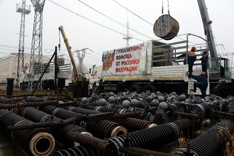 Employees of the Russian Emergency Ministry unload electrical equipment, part of a Russian convoy carrying humanitarian aid for the eastern Ukrainian Donetsk region, in the city of Makiyivka near Donetsk, on December 12, 2014 (AFP Photo/Vasily Maximov)