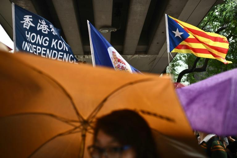 """A flag that reads """"Hong Kong Independence"""" is seen alongside the territory's British colonial-era flag and the pro-independence 'Estelada' Catalan flag during a march in Hong Kong on China's national day (AFP Photo/Anthony WALLACE)"""