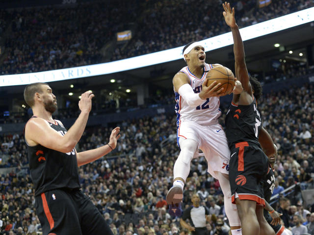 Philadelphia 76ers forward Tobias Harris (12) goes to the net against Toronto Raptors forward OG Anunoby (3) and center Marc Gasol (33) during the second half of an NBA basketball game, Wednesday, Jan. 22, 2020 in Toronto. (Nathan Denette/The Canadian Press via AP)