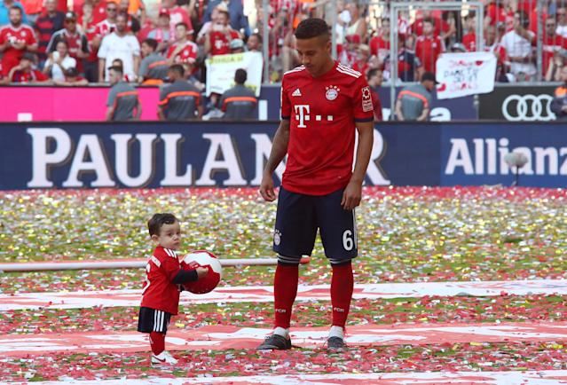 Soccer Football - Bundesliga - Bayern Munich v VfB Stuttgart - Allianz Arena, Munich, Germany - May 12, 2018 Bayern Munich's Thiago Alcantara celebrates winning the Bundesliga with his son REUTERS/Michael Dalder DFL RULES TO LIMIT THE ONLINE USAGE DURING MATCH TIME TO 15 PICTURES PER GAME. IMAGE SEQUENCES TO SIMULATE VIDEO IS NOT ALLOWED AT ANY TIME. FOR FURTHER QUERIES PLEASE CONTACT DFL DIRECTLY AT + 49 69 650050
