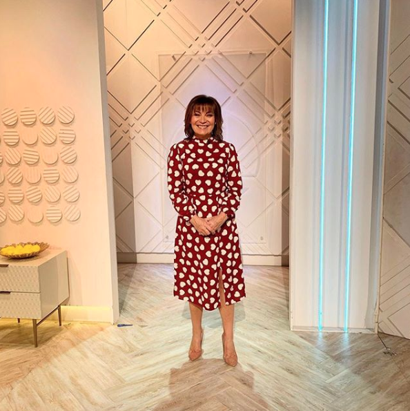 """<p>Lorraine is celebrating Valentine's Day in style with this absolute steal from Very.</p><p><strong>V by Very</strong></p><p>High Neck Midi Dress - Heart Print - £14.50</p><p><a class=""""body-btn-link"""" href=""""https://go.redirectingat.com?id=127X1599956&url=https%3A%2F%2Fwww.very.co.uk%2Fv-by-very-high-neck-midi-dress-heart-print%2F1600418785.prd&sref=http%3A%2F%2Fwww.prima.co.uk%2Fleisure%2Fcelebrity%2Fg30751501%2Florraine-kelly-fashion%2F"""" target=""""_blank"""">BUY NOW</a></p>"""