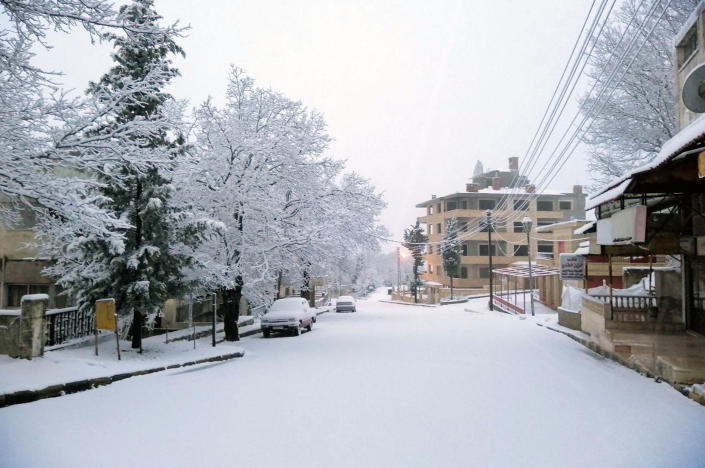 In this photo released by the Syrian official news agency SANA, snow covers a street in the town of Slanfah, in Latakia province, Syria, Wednesday, Feb. 17, 2021. Snow blanketed parts of Syria, Lebanon, Jordan and Israel on Wednesday, blocking roads, disrupting traffic and postponing vaccination campaigns against COVID-19 and even exams at some universities. (SANA via AP)