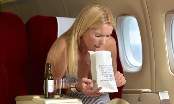 Woman being sick on plane with alcohol