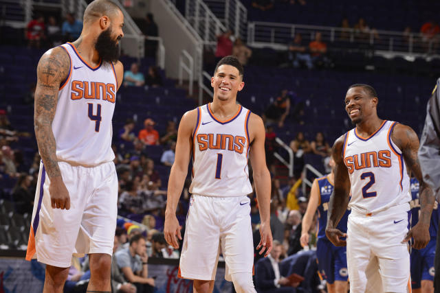Tyson Chandler talks with Devin Booker, middle, and Eric Bledsoe during a preseason game. (Getty Images)