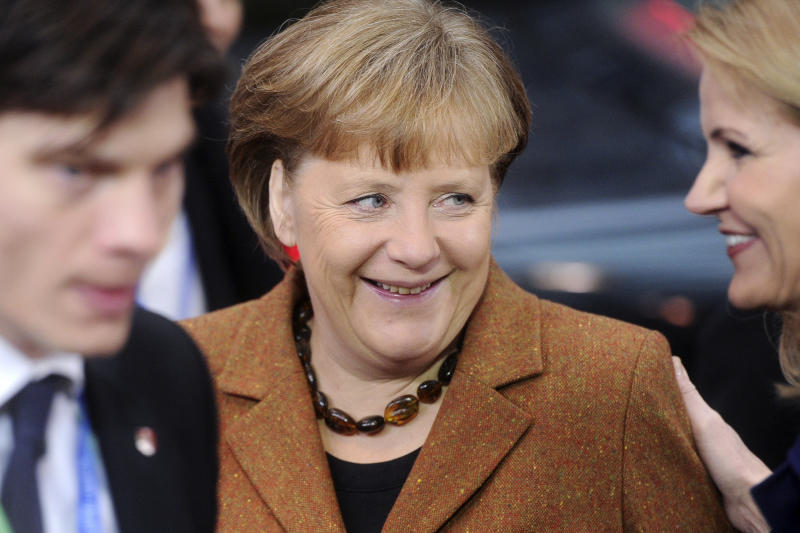 German Chancellor Angela Merkel, center, smiles at Denmark's Prime Minister Helle Thorning-Schmidt, right, as they arrive for an EU Summit in Brussels on Friday, March 2, 2012. The leaders of 25 European states have signed a new treaty designed to prevent the 17 euro countries from running up huge debts in order to prevent a repeat of the current crisis afflicting the single currency zone. Of the 27 European Union states, only Britain and the Czech Republic decided not to sign the treaty. (AP Photo/Geert Vanden Wijngaert)