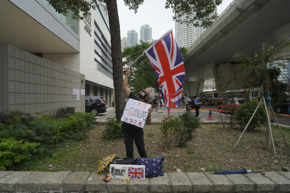 A pro-democracy supporter waves a British flag outside a court in Hong Kong Friday, April 16, 2021. Seven of Hong Kong's leading pro-democracy advocates, including 82-year-old veteran activist Martin Lee and pro-democracy media tycoon Jimmy Lai, are expected to be sentenced Friday for organizing a march during the 2019 anti-government protests that triggered an overwhelming crackdown from Beijing.(AP Photo/Kin Cheung)