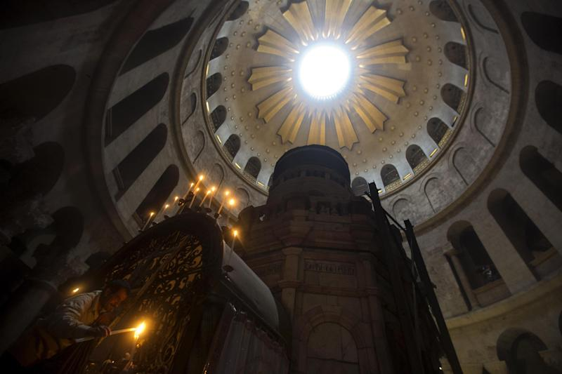 A worker lights candles prior to the Easter Sunday mass at the Church of the Holy Sepulchre, traditionally believed by many to be the site of the crucifixion and burial of Jesus Christ, in Jerusalem's Old City, Sunday, April 20, 2014. Millions of Christians around the world are celebrating Easter, commemorating the day when according to Christian tradition Jesus was resurrected in Jerusalem two millennia ago. (AP Photo/Sebastian Scheiner)