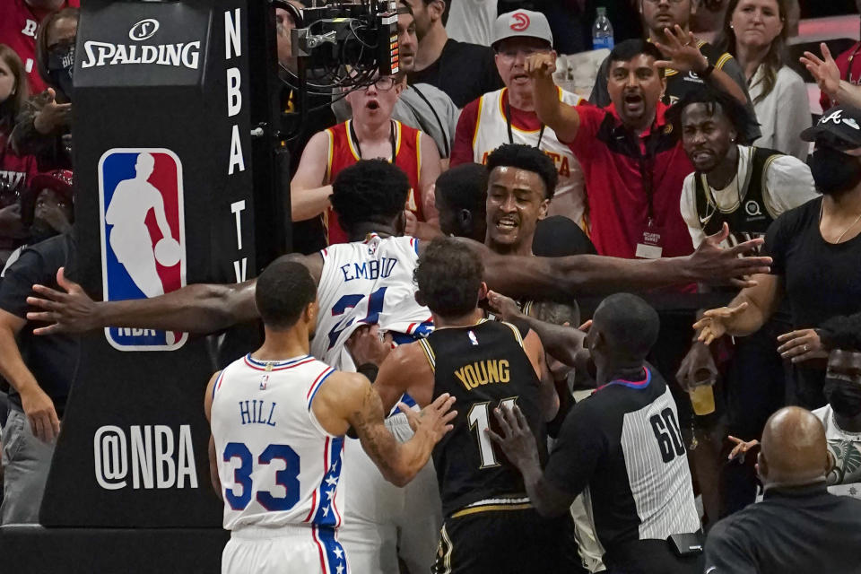 Philadelphia 76ers center Joel Embiid (21) and Atlanta Hawks forward John Collins (20) scuffle briefly during the second half of Game 6 of an NBA basketball Eastern Conference semifinal series Friday, June 18, 2021, in Atlanta. (AP Photo/John Bazemore)