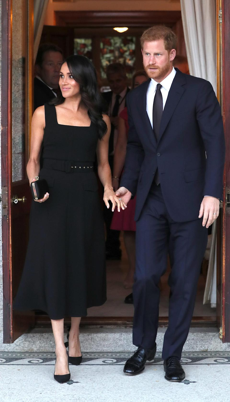 For a summer party at Glencairn House, the Duchess of Sussex changed into a black belted midi dress by Emilia Wickstead [Photo: Getty]