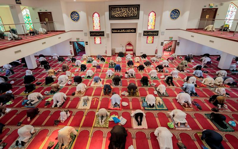 Worshippers observe social distancing at the Bradford Central Mosque on the first day of Eid, in Bradford, West Yorkshire, one of the areas where new measures have been implemented to prevent the spread of coronavirus. Stricter rules have been introduced for people in Greater Manchester, parts of East Lancashire, and West Yorkshire, banning members of different households from meeting each other indoors - Danny Lawson/PA