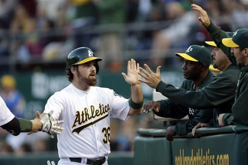 Oakland Athletics' Derek Norris is high-fived by teammates after scoring on a single from John Jaso during the second inning of a baseball game against the Texas Rangers on Monday, May 13, 2013 in Oakland. Calif. (AP Photo/Marcio Jose Sanchez)