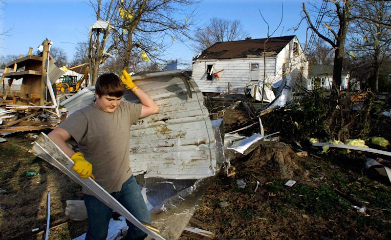 Jacob Brugger, 14, helps to salvage and clean up what he can Thursday, March 1, 2012, in Ridgway, Ill. A pre-dawn twister flattened entire blocks of homes Wednesday as violent storms ravaged the Midwest and South. (AP Photo/Seth Perlman)