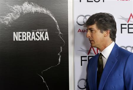 """Payne poses next to the poster for his film as he arrives for a gala screening of his new film """"Nebraska"""" at the AFI Fest 2013 in Hollywood"""