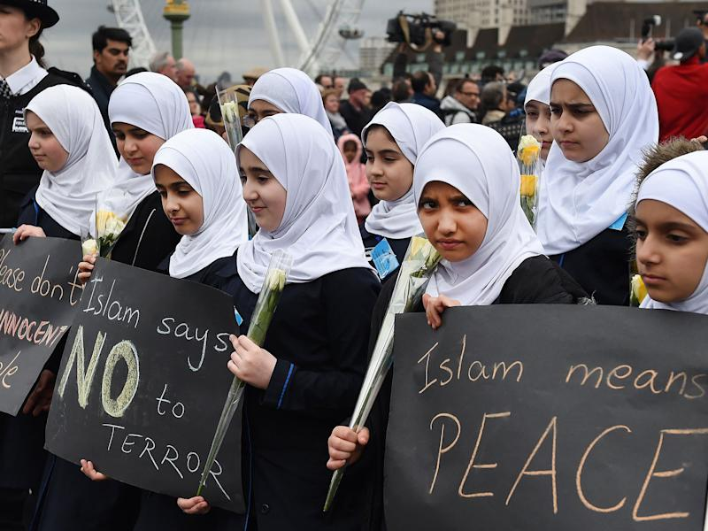 Muslim children carrying flowers join a vigil on Westminster Bridge in London on 29 March: EPA