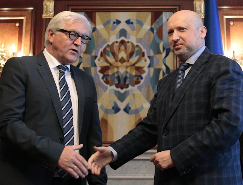 German Foreign Minister Frank-Walter Steinmeier, left, shakes hands with acting Ukrainian President Oleksandr Turchynov during a meeting in Kiev, Ukraine, Tuesday, May 13, 2014. Steinmeier flew to Ukraine Tuesday to help start talks between the Ukrainian government and its foes following the declaration of independence by two eastern region. (AP Photo/Sergei Chuzavkov)