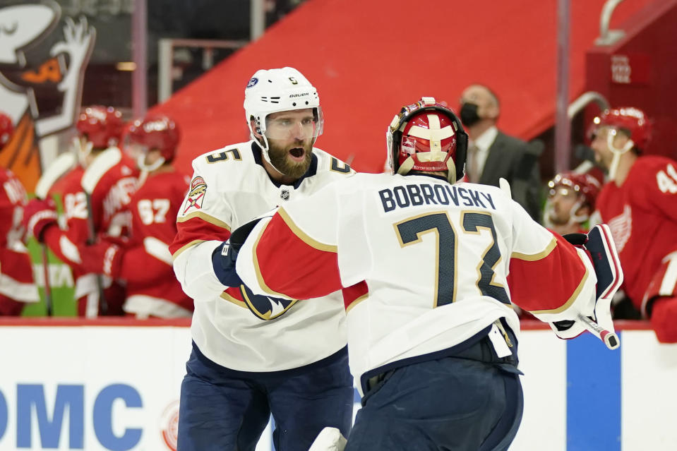 Florida Panthers defenseman Aaron Ekblad (5) congratulates goaltender Sergei Bobrovsky (72) after their overtime win over the Detroit Red Wings in an NHL hockey game, Saturday, Jan. 30, 2021, in Detroit. (AP Photo/Carlos Osorio)