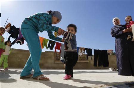 A Syrian refugee girl helps her brother, who the family suspects has polio, to walk in a mosque compound in Shebaa area, southern Lebanon