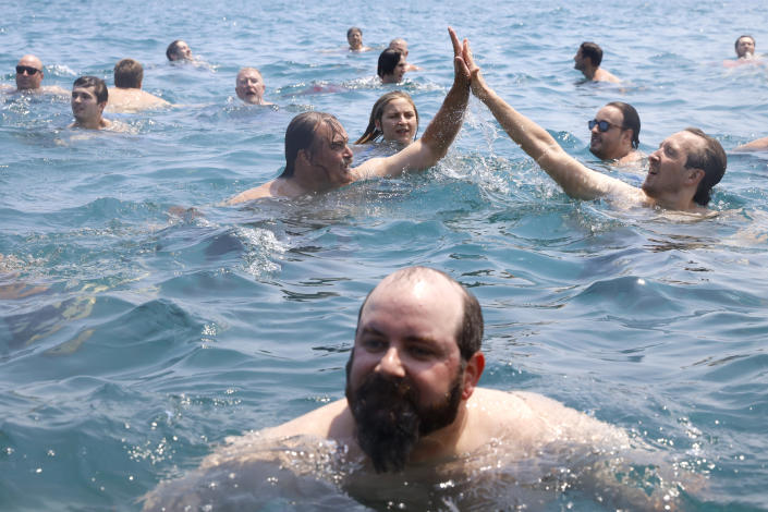 """Dan O'Conor, the """"Great Lake Jumper,"""" shares a """"High-5"""" with one of his well-wishers after his 365th leap into Lake Michigan, Saturday, June 12, 2021, in Chicago's Montrose Point. (AP Photo/Shafkat Anowar)"""