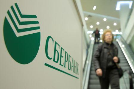 People walk down stairs past logo of Sberbank at its branch in Moscow