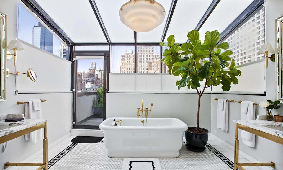 <p>Besides luxuries such as an oversized soaker tub, dual marble sinks and a rain shower, the bathroom's glass ceiling offers breathtaking views. (Douglas Elliman) </p>
