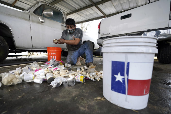 Martin Uribe, with West Street Recovery, sorts through plumbing repair parts while working to fix busted pipes which froze during the recent winter storm, at a home in Houston, Thursday, Feb. 25, 2021. West Street Recovery, a nonprofit created in the wake of Hurricane Harvey to help repair flood damaged homes, has been working since the winter storm hit to repair and replace damaged plumbing systems for residents who can't afford to do so. (AP Photo/David J. Phillip)