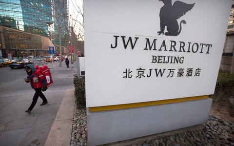 A deliveryman walks away from the entrance of a JW Marriott hotel in Beijing - Credit: AP