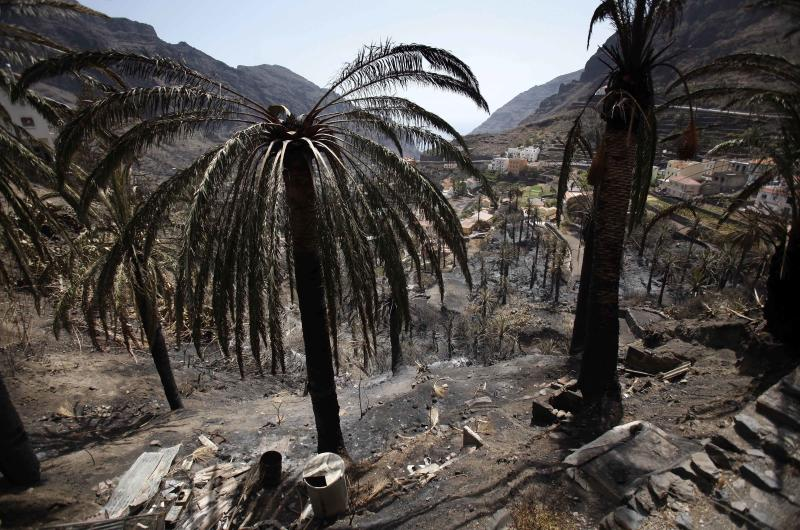 Houses are seen in a burned valley in  Barranco de Guada on the Canary island of La Gomera, Spain Tuesday Aug. 14, 2012.  Spanish authorities said Morocco sent two water-carrying planes to help in the battle to extinguish the wildfires that have torched some 3,000 hectares of land on the Canary Island of La Gomera, including areas of a UNESCO World Heritage Site national park. (AP Photo/Yaiza Mesa)
