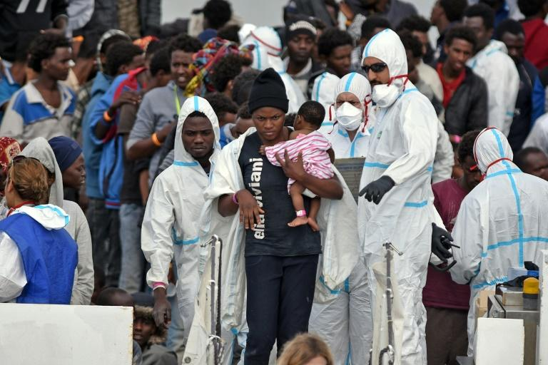 "A woman carries her baby as she disembarks from the Italian Coast Guard vessel ""Diciotti"" which landed hundreds of refugees rescued in the Mediterranean"