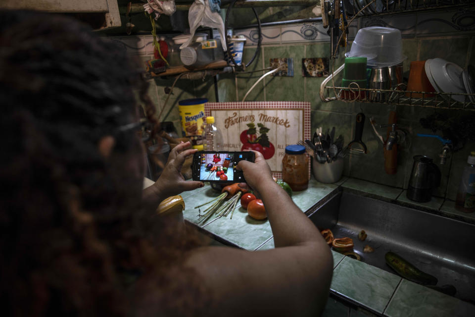 """Contributor Yuliet Colon takes pictures of ingredients to upload to the """"Recipes from the Heart"""" facebook page for her latest post, in her home in Havana, Cuba, Friday, April 2, 2021. Colon bought the few vegetables she could find at an agricultural market near her home, and used them to create something that she called """"Cuban-style pisto manchego."""" (AP Photo/Ramon Espinosa)"""
