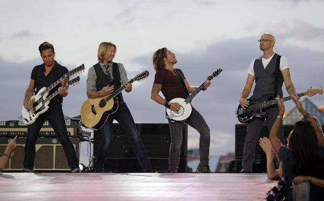 Keith Urban, second from right, performs during an NFL Kickoff event, Thursday, Sept. 5, 2013, in Baltimore, to celebrate the season-opening NFL football game between the Baltimore Ravens and the Denver Broncos in Denver. (AP Photo/Patrick Semansky)