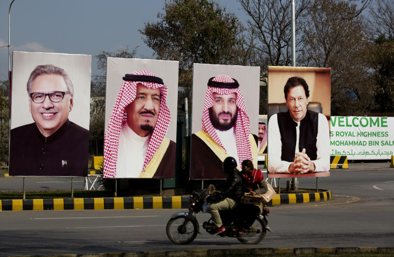 Pakistani riders drive past portraits of Pakistani and Saudi leaders display on the occasion of the visit by Saudi Arabia's Crown Prince to Pakistan, in Islamabad, Pakistan, Friday, Feb. 15, 2019. Pakistan said Wednesday that Crown Prince Mohammed bin Salman will arrive in Islamabad later this week on an official visit that is expected to include the signing of agreements for billions of dollars of investment in Pakistan. (AP Photo/B.K. Bangash)