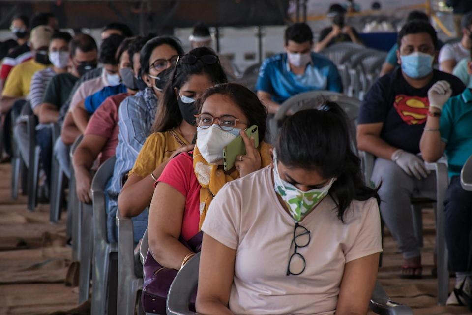 Young Indians wait to get vaccinated against the coronavirus at Radha Soami Satsang Ground in New Delhi on WednesdayAP