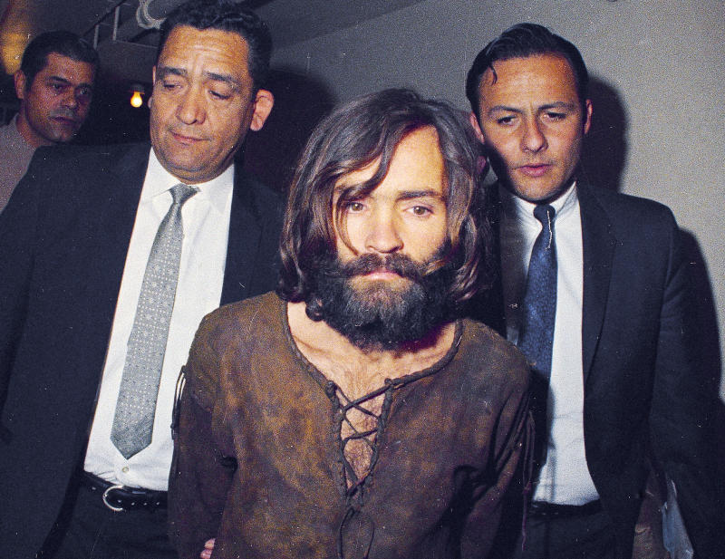 FILE - In this 1969 file photo, Charles Manson is escorted to his arraignment on conspiracy-murder charges in connection with the Sharon Tate murder case in Los Angeles. Fifty years ago Charles Manson dispatched a group of disaffected young hippie followers on a two-night killing spree that terrorized Los Angeles and in the years since has come to represent the face of evil. On successive nights in August 1969, the so-called Manson family murdered seven people. (AP Photo/File)