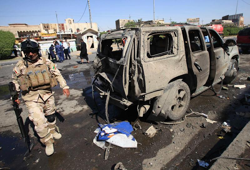 An Iraqi soldier inspects the site of a car bomb attack in Basra, 340 miles (550 kilometers) southeast of Baghdad, Iraq, Sunday, Oct. 13, 2013. A string of bombings in mostly Shiite-majority cities across Iraq on Sunday killed and wounded dozens of people, officials said, a grim reminder of the government's failure to stem the uptick in violence that is feeding sectarian tensions in the country.(AP Photo/Nabil al-Jurani)