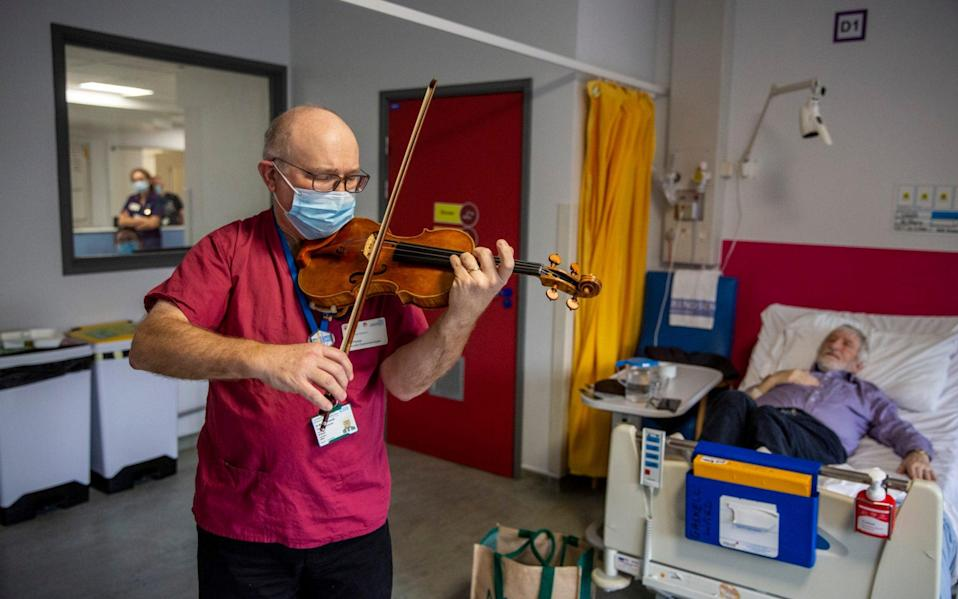 Dr Maxton Pitcher, a Consultant Gastroenterologist at Northwick Park Hospital London ,has been playing his violin for the benefit of patients and hospital staff since the pandemic began - Telegraph/Heathcliff O'Malley