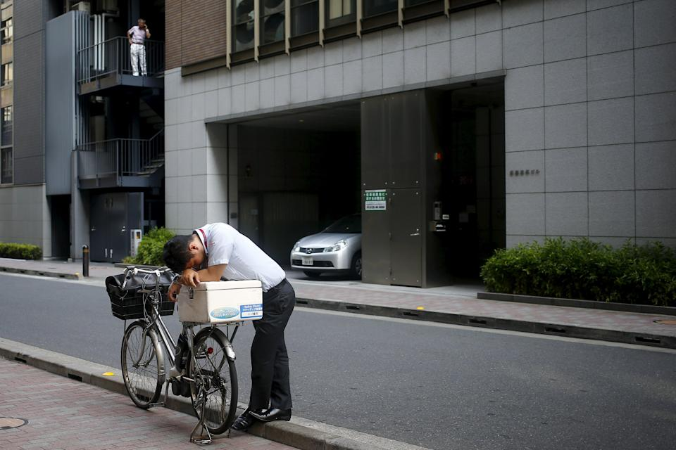 A businessman rests his head on a bike in the central district of Ginza in Tokyo, August 3, 2015. REUTERS/Thomas Peter