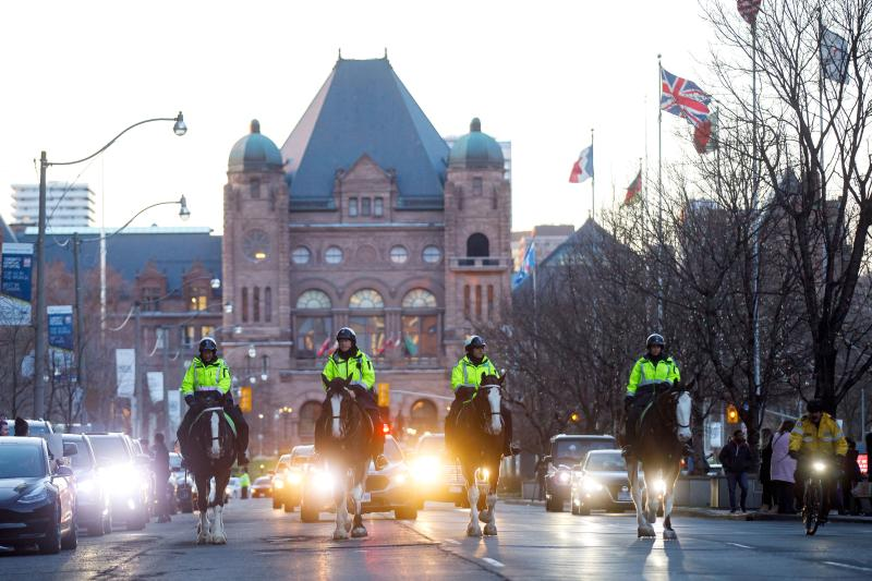 Mounted police officers ride down University Ave. through hospital row as Toronto first responders parade in front of the hospitals in Toronto, Ontario, Canada, in a salute to healthcare workers on April 19, 2020, amid the novel coronavirus pandemic. - The worldwide death toll from the novel coronavirus pandemic rose to 164,016 on April 19, according to a tally from official sources compiled by AFP at 1900 GMT. (Photo by Cole BURSTON / AFP) (Photo by COLE BURSTON/AFP via Getty Images)