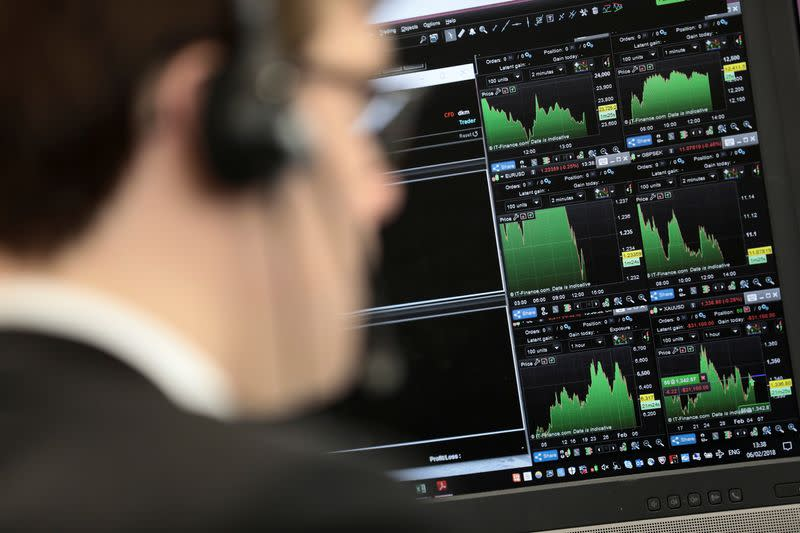 A broker looks at financial information on computer screens on the IG Index the trading floor