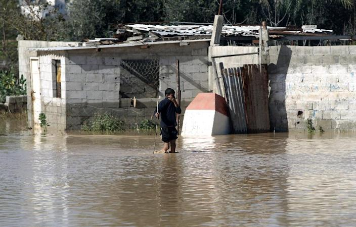 A Palestinian Bedouin boy walks through a flooded street in Mughraqa, south of Gaza City, on February 22, 2015 (AFP Photo/Mahmud Hams)
