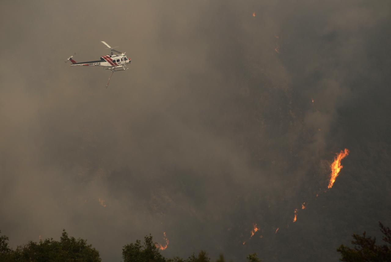 A California Department of Forestry helicopter flies over a wildfire burning on Pfeiffer Ridge in Big Sur, California, December 17, 2013. Crews battling the wildfire along central California's scenic Big Sur coastline were on guard against a possible shift in winds on Tuesday, after the blaze destroyed at least 15 dwellings and forced 100 people to flee their homes, fire and county officials said. REUTERS/Michael Fiala (UNITED STATES - Tags: ENVIRONMENT DISASTER TRANSPORT TPX IMAGES OF THE DAY)