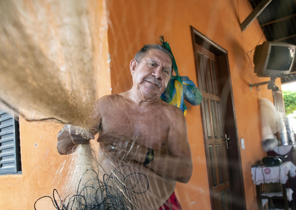 Fisherman Alfredo Jose Branco fixes his net at his home in Alter do Chao, district of Santarem, Para state, Brazil, Thursday, Aug. 27, 2020. Branco was born and raised in this once-isolated Brazilian Amazon district, a tropical paradise that blends dense rainforest and beaches by the clear waters of the Tapajós river. (AP Photo/Andre Penner)