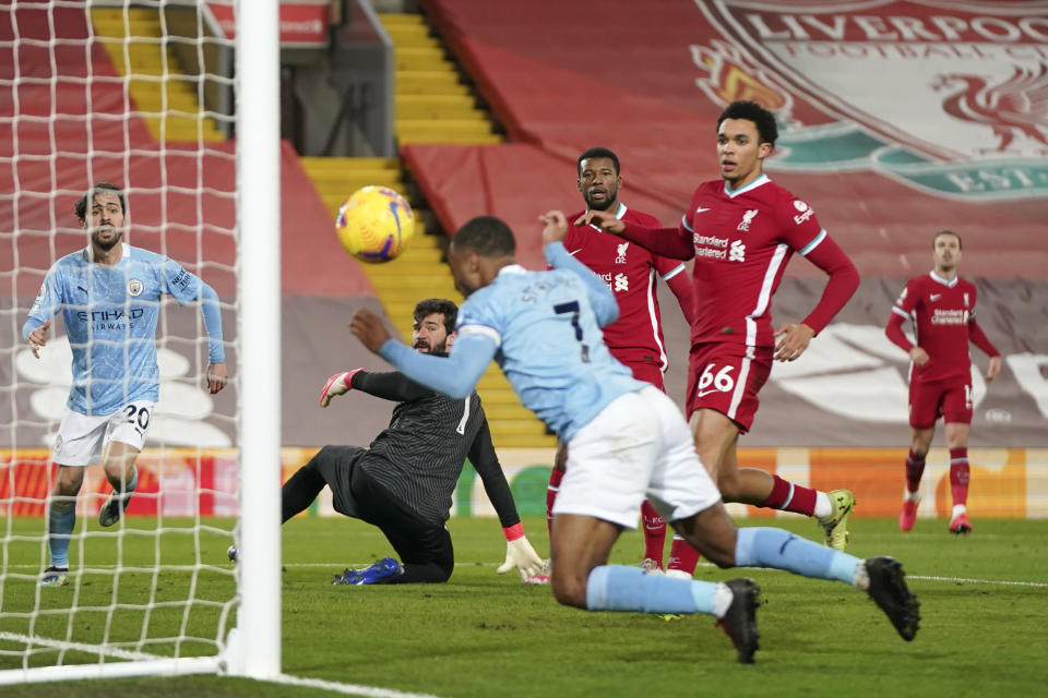 Manchester City's Raheem Sterling, foreground, scores his side's third goal during the English Premier League soccer match between Liverpool and Manchester City at Anfield Stadium, Liverpool, England, Sunday, Feb. 7, 2021. (AP photo/Jon Super, Pool)