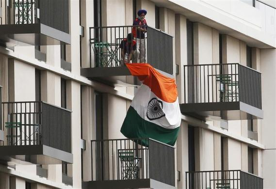 Men hang an Indian flag from a balcony in the Athletes' Village, ahead of the Olympic Games in the London 2012 Olympic Park at Stratford in London July 17, 2012.
