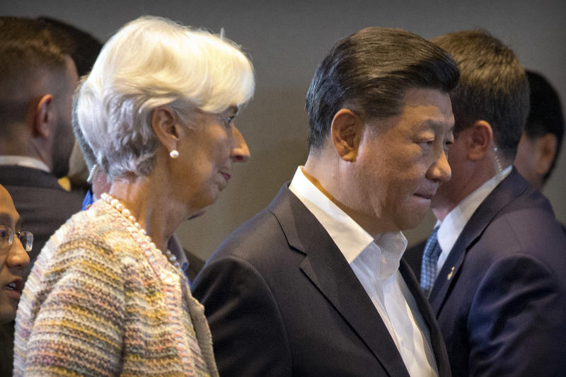 IMF managing director Christine Lagarde, left, and Chinese President Xi Jinping arrive for an International Monetary Fund (IMF) informal dialogue session at APEC Haus in Port Moresby, Papua New Guinea, Sunday, Nov. 18, 2018. (AP Photo/Mark Schiefelbein)